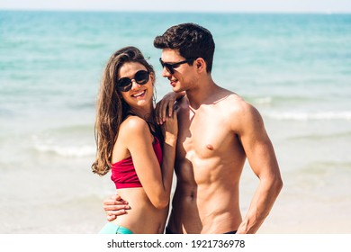 Vacation romantic lovers young happy couple hug and standing on sand at sea having fun and relaxing together on tropical beach.Summer vacations