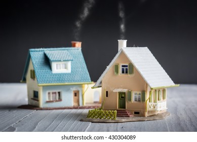 Vacation and secondary homes - Mortgage concept - Two miniature houses against a black background.