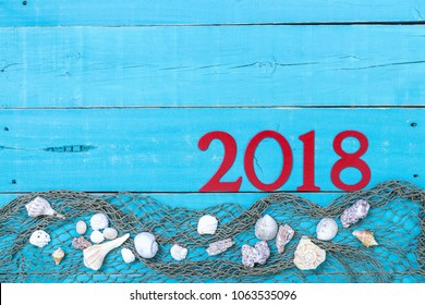 Vacation sign with 2018 in bold red with seashells and fish netting border on rustic antique teal blue wood background; travel concept message board with copy space