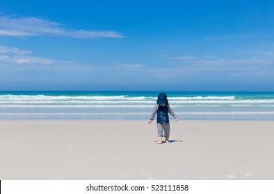 vacation with small kids concept, cute toddler wearing sun protective costume playing with sand and water on beach of paradise destination