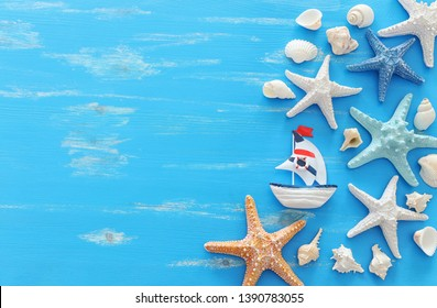 vacation and summer concept with vintage boat starfish and seashells over blue wooden background. Top view flat lay