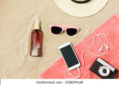 vacation and summer holidays concept - smartphone with earphones and film camera on towel, straw hat, sunglasses and bottle of sunscreen oil on beach sand