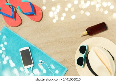 vacation and summer holidays concept - smartphone with earphones on towel, straw hat, sunglasses, flip flops and bottle of sunscreen oil on beach sand