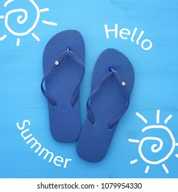 vacation and summer image with flipflops over blue wooden background