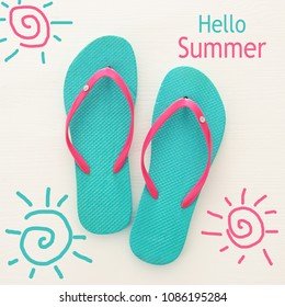 vacation and summer image with flipflops over white wooden background