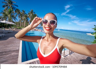 Vacation and technology. Colorful portrait of pretty young woman taking selfie portrait near swimming pool on tropical beach.