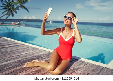 Vacation and technology. Colorful portrait of pretty young woman taking selfie portrait with her  smartphone near swimming pool on tropical beach.