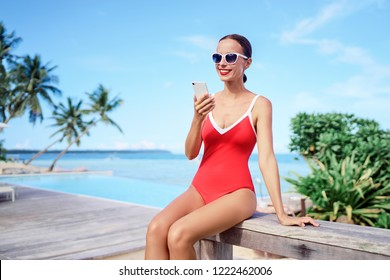 Vacation and technology. Colorful portrait of pretty young woman using smartphone near swimming pool on tropical beach.