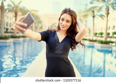 Vacation and technology. Pretty young woman using smartphone taking selfie in Dubai Downtown.