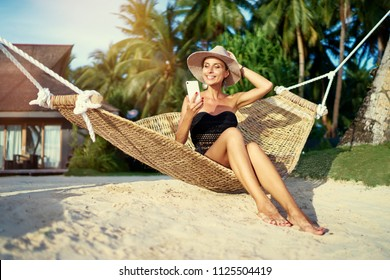 Vacation and technology. Young pretty woman in hat and swimsuit using smartphone laying in hammock on the beach.