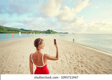 Vacation and technology. Young woman taking photo of beautiful tropical beach on smartphone.