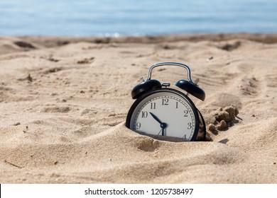 Vacation time. Alarm clock on the sand beach.