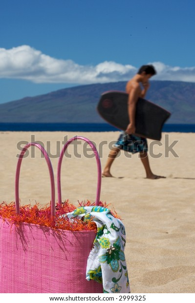 Vacation Time beach bag sitting on a beach with summer fabric hanging out and a island in the background against a blue sky with with clouds with a boogie boarder walking in the background