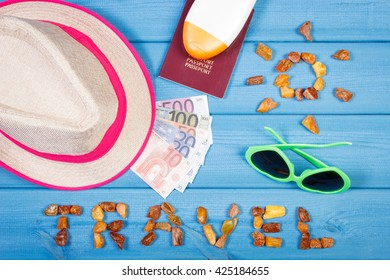 Vacation time. Inscription travel and shape of sun made of amber stones, passport with currencies euro, sunglasses, straw hat and sun lotion