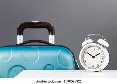 Vacation time. White alarm clock near green suitcase isolated on gray background.