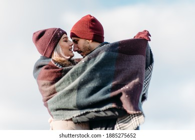 Vacation together. Young hipster couple. Woman kissing nose her boyfriend. Winter love story, a beautiful stylish young couple.