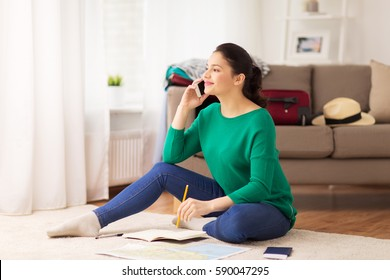 vacation, tourism, travel and people concept - happy young woman with notebook, passport and map calling on smartphone at home