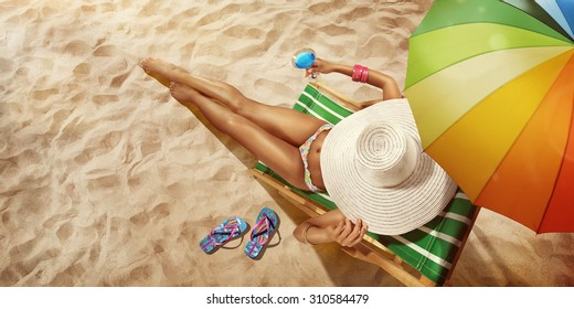 Vacation. Travel. Beautiful young woman relaxing on beach chair with cocktail. Top view