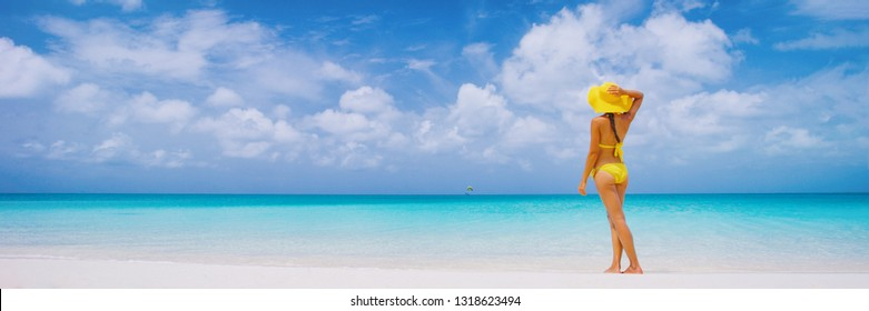 Vacation travel bikini woman on Caribbean beach. Lady with slim sexy body standing on tropical white sand beach in Caribbean looking at perfect turquoise ocean. Luxury destination.