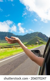 Vacation and travel concept. Woman driver feeling the wind through her hands while driving in the country side.