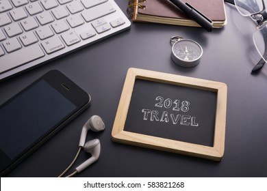 Vacation and travel concept.2018 TRAVEL written on small chalkboard and smart phone,earphone,compass,glasses,notebook,pen,keyboard on the grey background