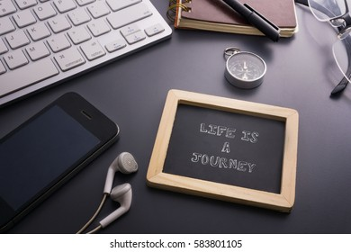 Vacation and travel concept.LIFE IS JOURNEY written on small chalkboard and smart phone,earphone,compass,glasses,notebook,pen,keyboard on the grey background