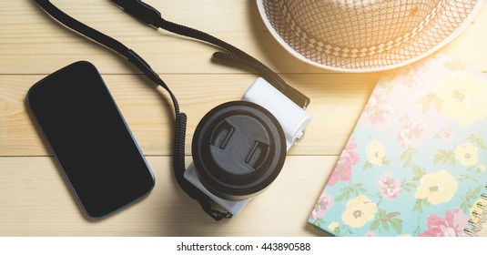Vacation travel equipment on wooden background.