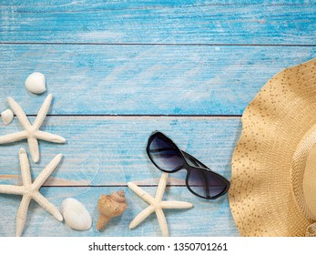 Vacation travel equipment Straw hat, sunglasses And marine objects, shells, starfish On a blue wooden floor