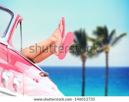 Vacation travel freedom beach concept with cool convertible vintage car and woman feet out of window against tropical see background with palm trees. Girl relaxing enjoying free holidays.