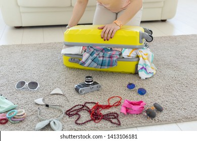 Vacation, travel and holidays concept - Woman trying to close suitcase with a lot of things