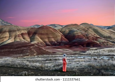 Vacation travel in Oregon. Woman enjoying the view of beautiful Painted Hills at sunset. John Day Fossil Beds National Monument Bend. Or. United States of America