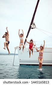 vacation, travel, sea, friendship and people concept – Happy friends jumping from sailing boat in sea.