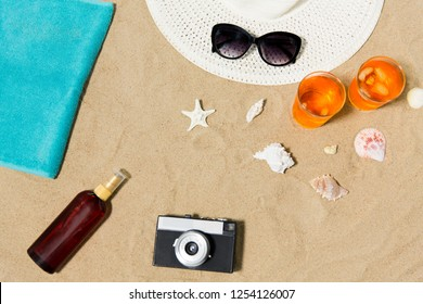 vacation, travel and summer concept - two glasses of aperitif cocktails with ice, sun hat with sunglasses, vintage film camera with sunscreen oil and seashells on beach sand