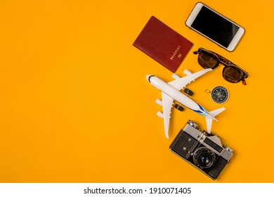 Vacation travel summer trip concept. Minimal simple flat lay with a toy airplane, vintage camera, passport on a yellow background. Tourist essentials