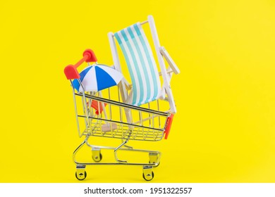 Vacation travel tour sale concept. Tourism opening. Sun lounger and summer umbrella in a shopping cart on trendy yellow background.