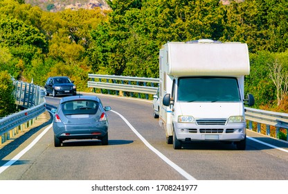 Vacation trip with Caravan Car on road in Italy. Camper and Summer drive on highway. Holiday journey in rv motorhome for recreation. Motor home minivan motion ride. Scenery with mini van vehicle.
