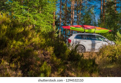 Vacation Trip with Kayaks. SPort Utility Vehicle with Two Large Kayaks on the Roof Rack. Summer Recreation Theme.