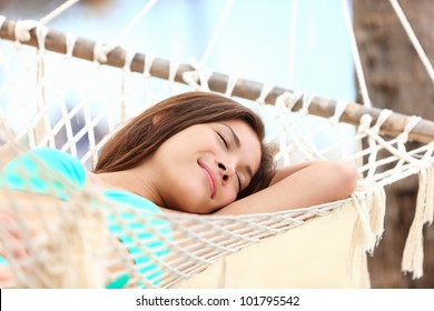 Vacation woman lying in hammock relaxing and sleeping smiling happy during summer holidays in tropical resort. Mixed race Asian / Caucasian girl in bikini.
