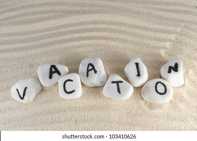 Vacation word on group of stones with sand as background