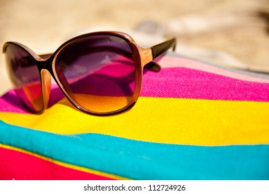 vacations concept with bag and glasses on the sand