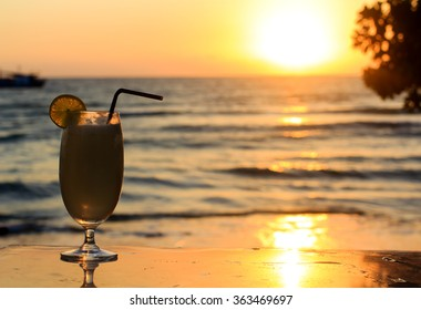 Vacations in Thaillande : backlit glass with cocktail with sunset over the sea on the background.