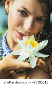 Vacations, travel, relaxation. Woman with blue eyes with white water lily in hand