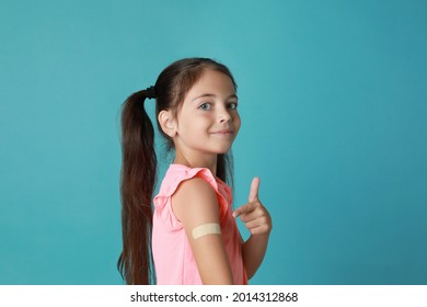 Vaccinated little girl showing medical plaster on her arm against light blue background