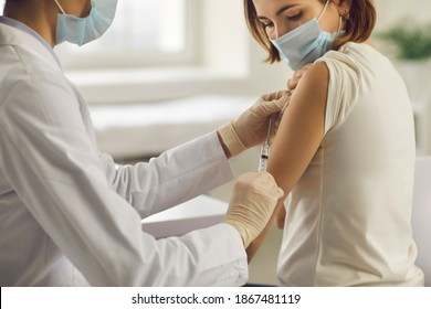 Vaccination, immunization, disease prevention concept. Patient getting Covid-19 vaccine at doctor's office. Cropped shot of professional nurse in medical face mask giving flu injection to young woman