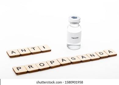 Vaccine concept showing a medical vial with a Vaccine label on a white background along with a sign reading Anti Propaganda