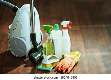 vacuum cleaner, cleaning bottles, rubber gloves, brush and cleaning cloth on floor.