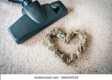 Vacuum cleaner head closeup and a dust heart on white carpet. Household and cleaning concept.