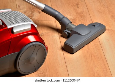 Vacuum cleaner on floating floor - close-up of noozle and hoover