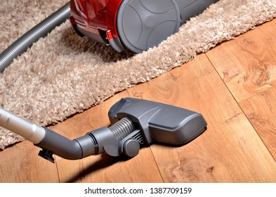 Vacuum cleaner on floating floor and shaggy carpet