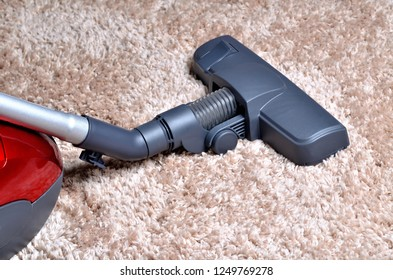 Vacuum cleaner on shaggy carpet - close-up of noozle and hoover